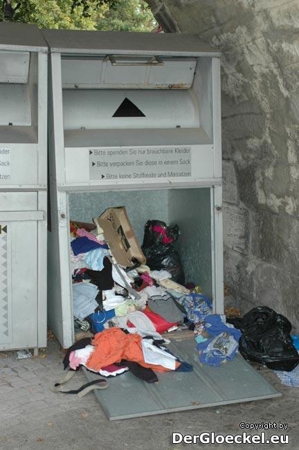 Bei diesem geöffneten Alttextilbehälter suchte die Frau mit ihrem Kind nach Kleidung