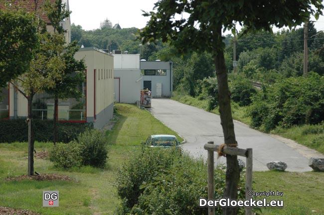 """Das Freiluftklo parallel zur Asphaltstraße beim Grünstreifen hinter dem Gebäude, das BILLA, BIPA, KIK und das Wettbüro beherbergt. Auf der Stirnseite, das Gebäude vom SPAR mit """"Eckklo"""""""