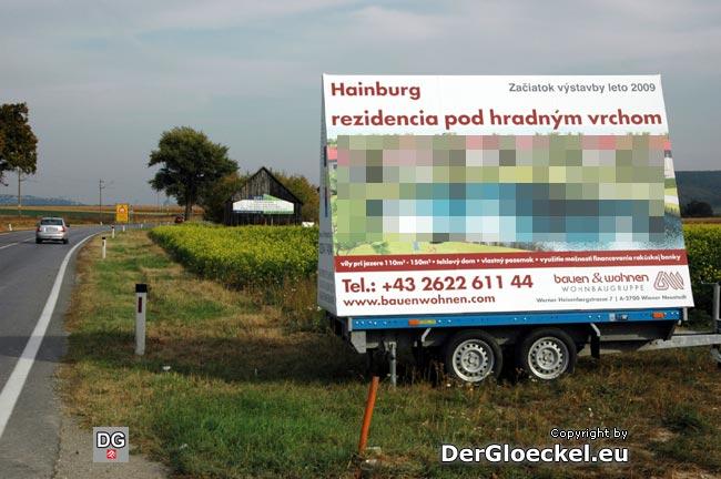 Die illegale Werbung der Bauen & Wohnen Wohnbau GmbH - im Hintergrund am Stadl die noch immer nicht abmontierte, ebenso rechtswidrig angebrachte Werbung, der WM-Real Immobilien GmbH. Man beachte zusätzlich, daß diese Werbungen sich in einem ausgewiesenen Gefahrenbereich befinden, der durch die gelbe, links im Bild erkennbare, Warntafel bezeichnet wird.